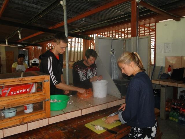 Matt, Kelby, and Jana chopping vegetables as community volunteers