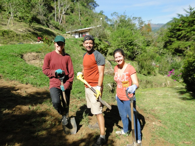 Joao (center)  takes the lead role in supervising other volunteers on a task in the yard